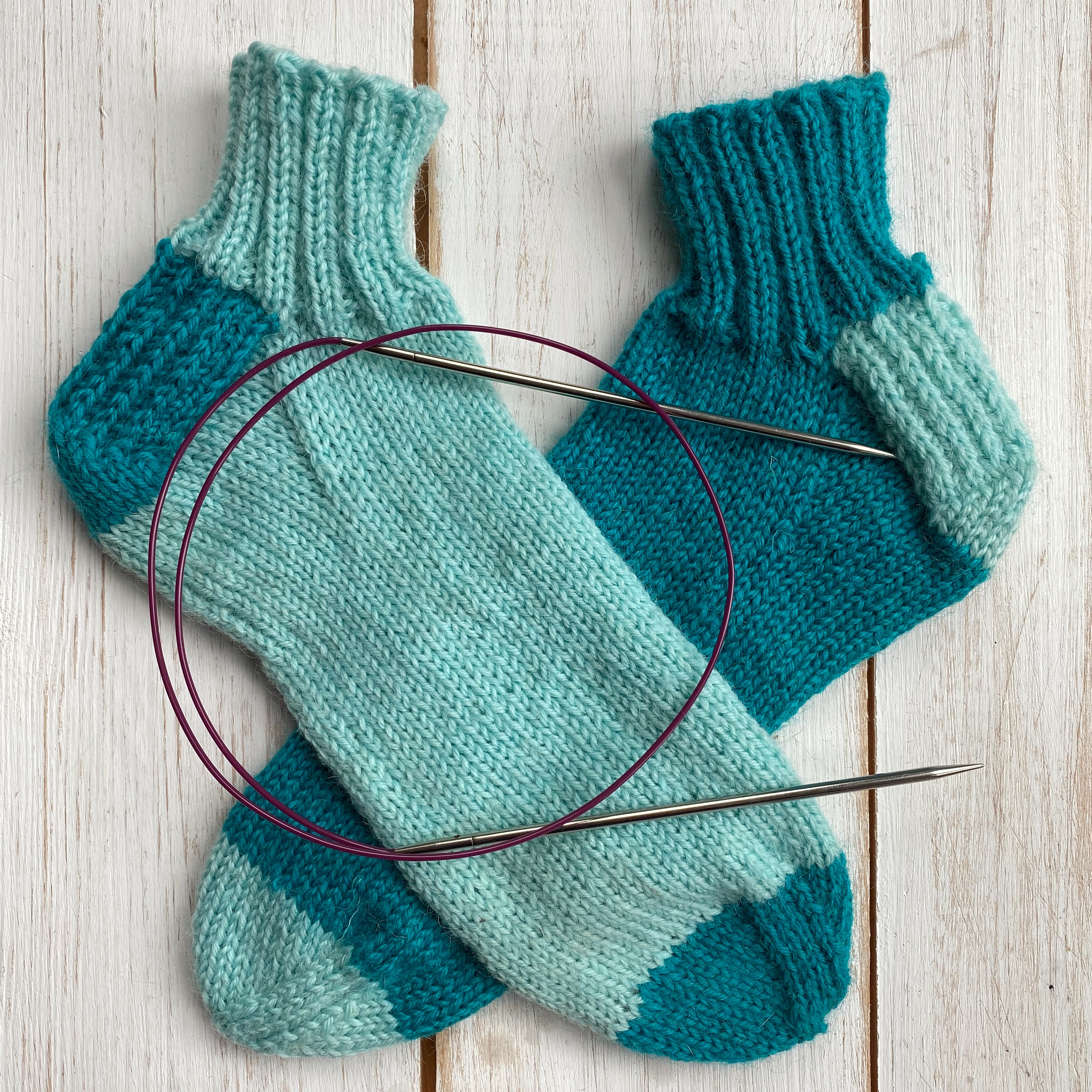 two hand knitted socks and a circular knitting needle